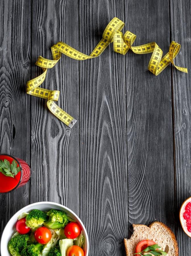 Concept slimming diet fresh vegetables on wooden background top view. Concept slimming diet fresh vegetables on dark wooden background top view stock images