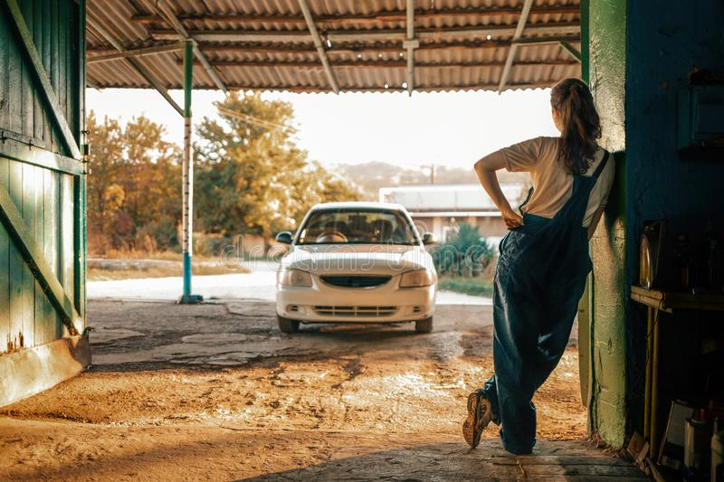 The concept of small business, feminism and women`s equality. Young woman mechanic resting leaning against the wall. In the. Background, a car and a street royalty free stock images