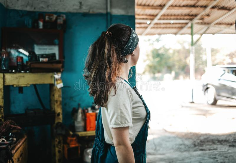 The concept of small business, feminism and women`s equality. A young woman in work clothes looks at the street from an auto royalty free stock image