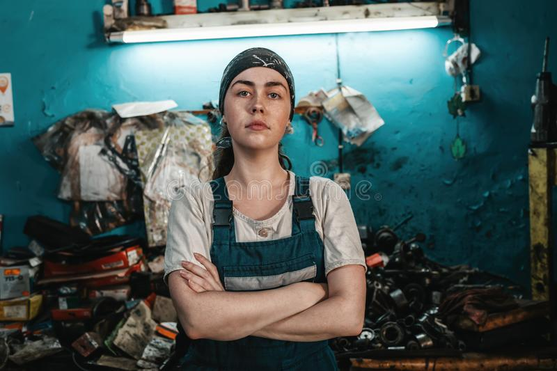 The concept of small business, feminism and women`s equality. A young woman in working clothes posing in front of a car workshop. stock photo