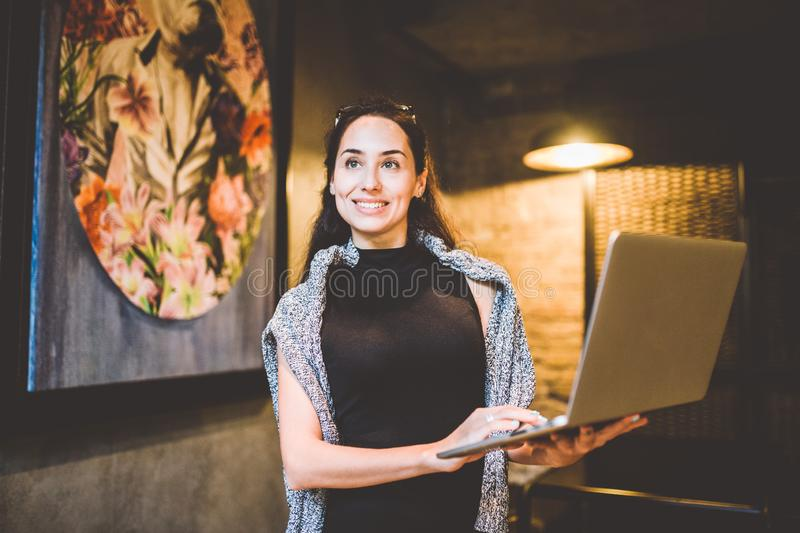 The concept of small business and technology. Young beautiful brunette businesswoman in black dress and gray sweater stands in royalty free stock image
