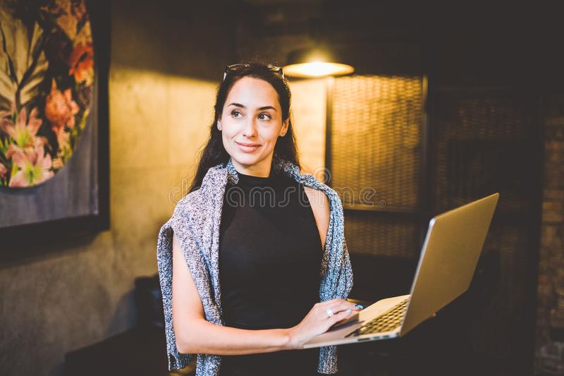 The concept of small business and technology. Young beautiful brunette businesswoman in black dress and gray sweater stands in stock images