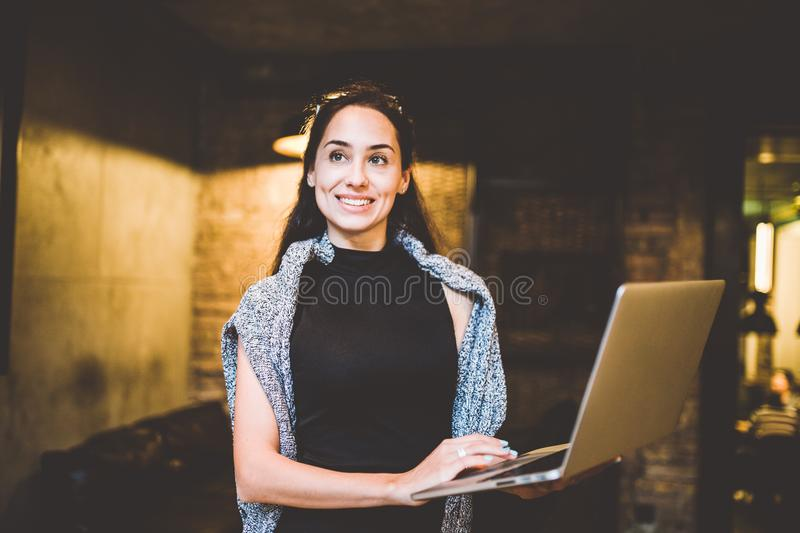The concept of small business and technology. Young beautiful brunette businesswoman in black dress and gray sweater stands in cof stock images