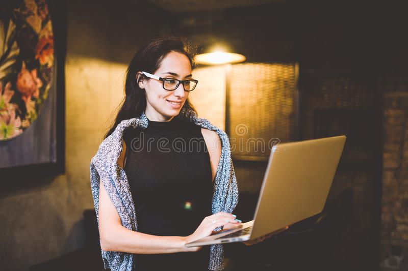 The concept of small business and technology. Young beautiful brunette woman in black dress and gray sweater stands in coffee shop royalty free stock images