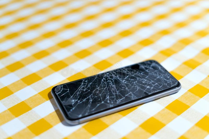 Concept of smart phone with broken screen. Top view on yellow background. Cracked, shattered lcd touch screen on modern cellphone. Gadget needs repairing stock photo