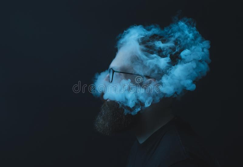 Concept. Smoke enveloped the head man. Portrait of a Bearded, stylish man with smoke. Secondhand smoke. royalty free stock photos