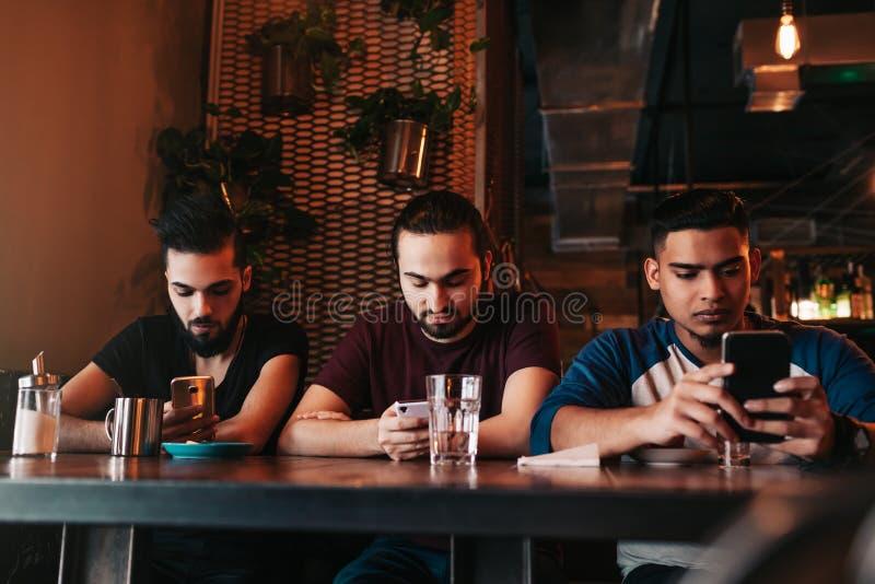 Concept social de dépendance de réseau Amis de métis regardant leurs téléphones dans la barre Types Arabes employant des smarphon image stock