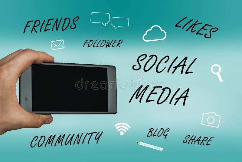 Concept social de media avec la main tenant le périphérique mobile et les icônes photo stock