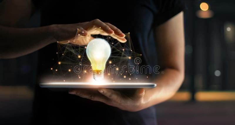 Concept social de medias Mains avec le comprimé, ampoule lumineuse photo libre de droits