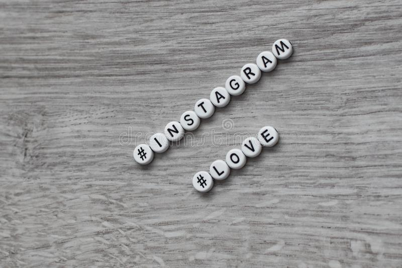 The concept of a social network of instagram in the form of separate circular letters of the alphabet on a wooden background. Insc. Ription instagram love royalty free stock photos