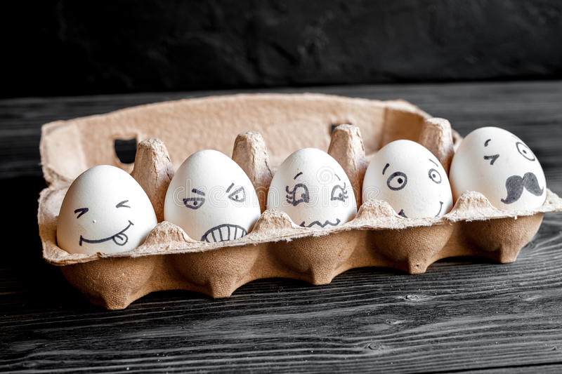 Concept social networks communication and emotions - eggs. On dark wooden background stock photos