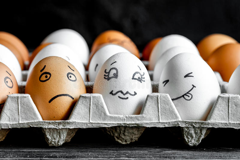 Concept social networks communication and emotions - eggs smile. On dark wooden background stock images