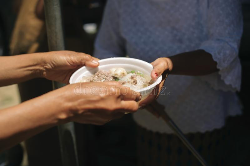 The concept of social sharing : Poor people receiving food from donations : Homeless people are helped with food relief, famine. Relief : volunteers giving food royalty free stock photo