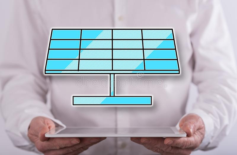 Concept of solar energy. Solar energy concept above a tablet held by a man in background royalty free stock photo