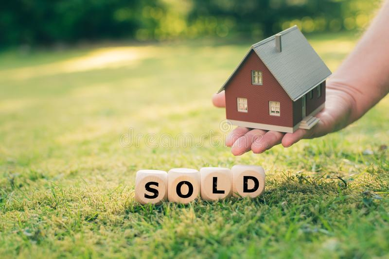 Concept of a sold house. A hand holds a model house above a meadow. Dice form the word `SOLD royalty free stock photos