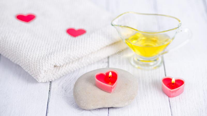 The concept of a Spa on Valentine`s Day. Red heart-shaped candles, stones, massage oil and a white towel on a wooden stock image