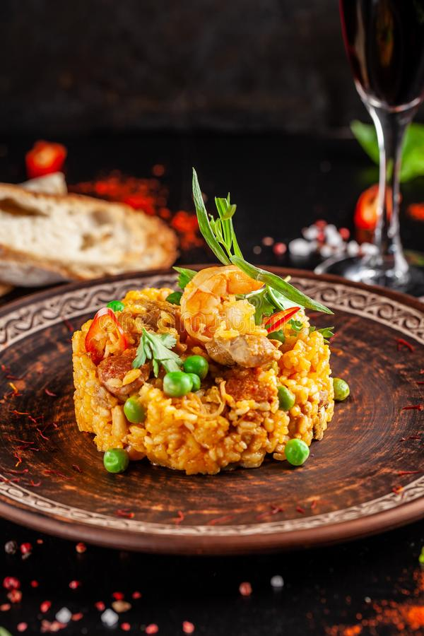 Concept of Spanish cuisine. Paella with seafood and shrimps, with green peas in a clay plate. A glass of cool wine is on the table. Background image, copy royalty free stock image