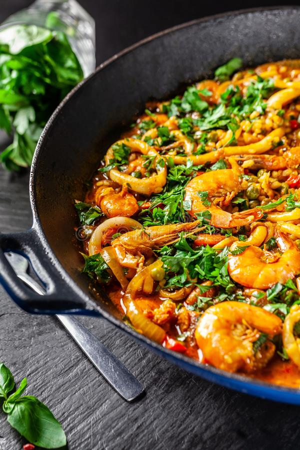 Concept of Spanish cuisine. Paella with seafood, shrimps, squid and greens, cooked in wok pan on street. street food stock images