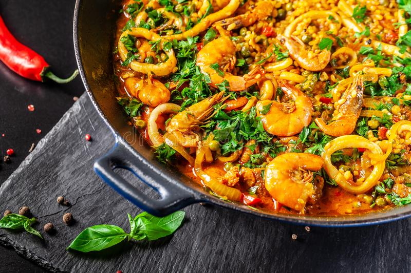 Concept of Spanish cuisine. Paella with seafood, shrimps, squid and greens, cooked in a wok pan on the street. street food. The concept of Spanish cuisine stock images