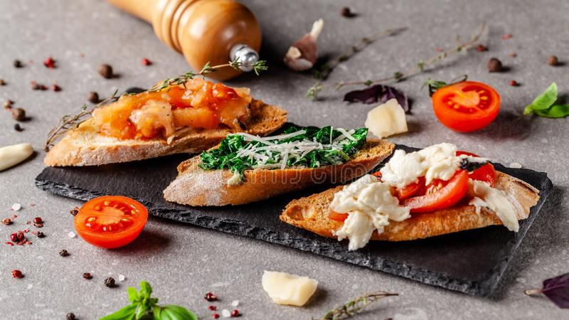 Concept of Spanish cuisine. Tapas Different bruschetta on a fried baguette with basil, tomatoes, cheese. Serving dishes stock image
