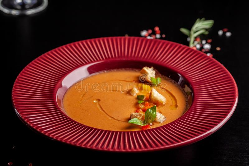 Concept of Spanish cuisine. Tomato soup Gazpacho from fresh tomatoes. Beautiful serving dishes in a red plate on a black table royalty free stock images