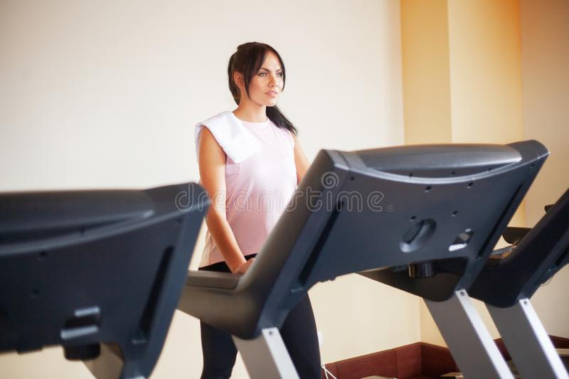 Concept of sport and healthy lifestyle. Young attractive fitness woman running on treadmill, wearing in white sportswear stock images