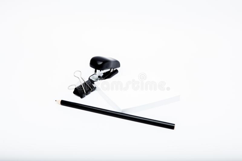 Concept stationnaire, photo plate de vue supérieure de configuration de crayon, trombones agrafés et, notes sur le fond blanc ave photographie stock