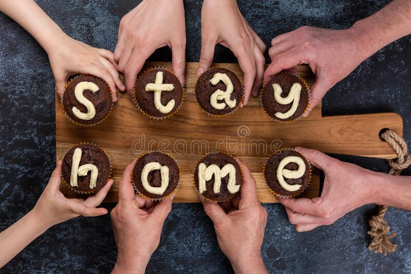 Concept Stay Home. Concept flat lay Stay Home. Many hands of different ages of people reach out and hold chocolate muffins, with cream letters. Eight cupcakes stock images
