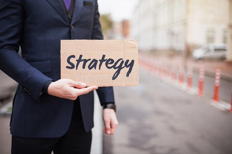 The concept of strategy. A young businessman in a business suit holds a sign in his hand royalty free stock photos