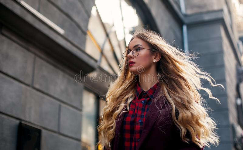 The concept of street fashion. Young beautiful model in the city. Beautiful blond woman wearing sunglasses. Hair fluttering in the royalty free stock photos