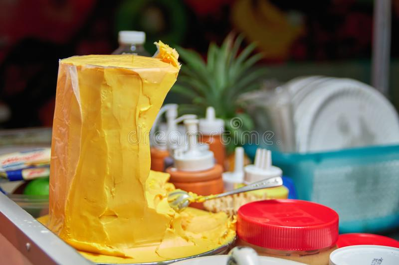 Concept of street food in Asia. Big chunk of palm oil on the pancake dealer`s counter. Fast food. Copy space royalty free stock image