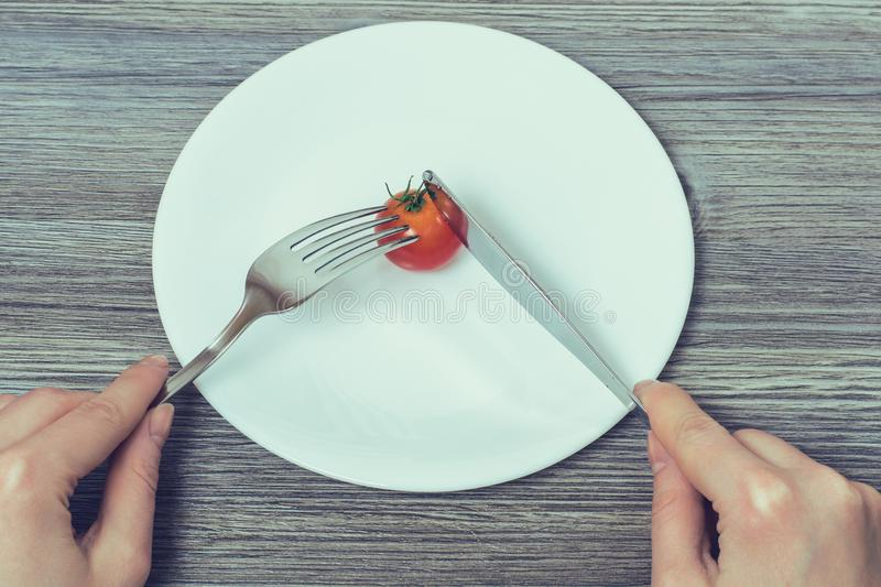 Concept of strict dieting. Woman`s hands cutting little cherry t stock photos