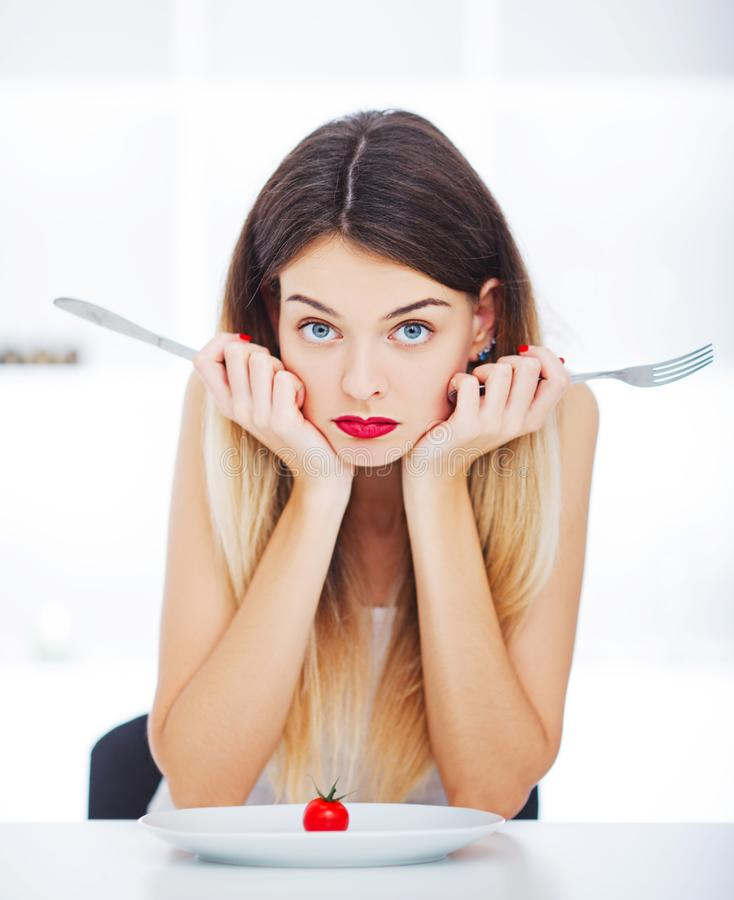 Diet. Concept of strict dieting. Woman`s hands trying to cut lit royalty free stock photos
