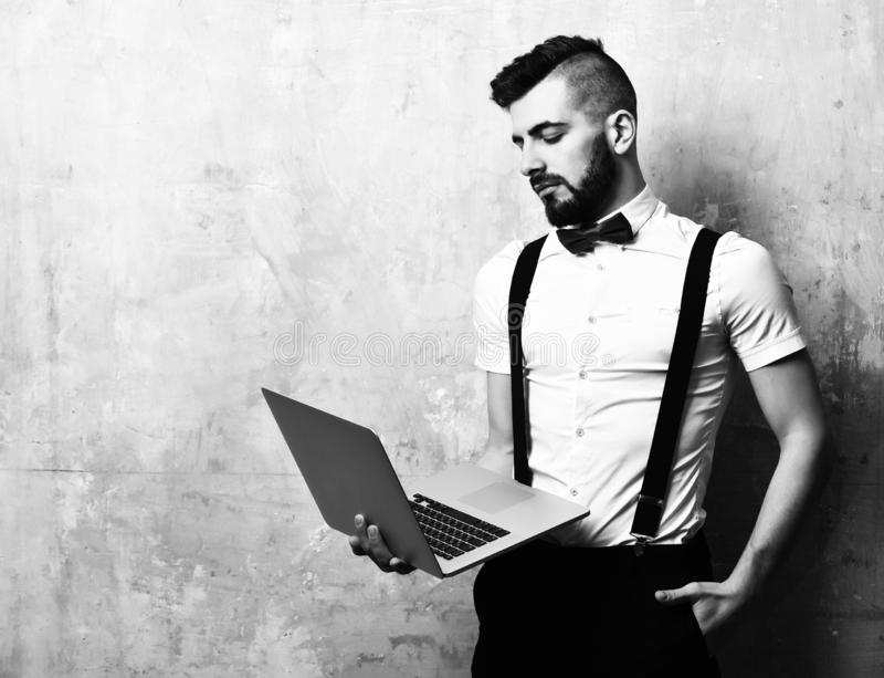 Concept of style and management. Guy with beard in white shirt looks at display. Concept of style and management. Guy with beard in white shirt and suspenders stock photos