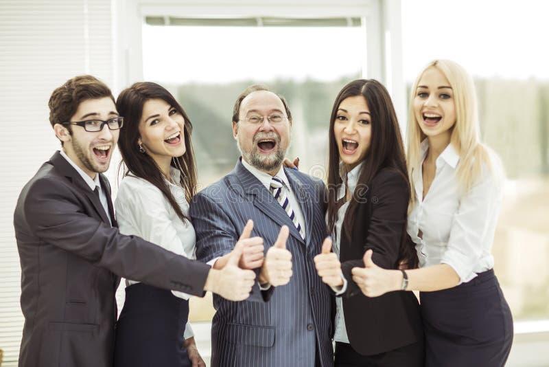 Concept succes in zaken: het chef- en zegevierend commerciële team maakt omhoog de gebaarduimen royalty-vrije stock afbeelding