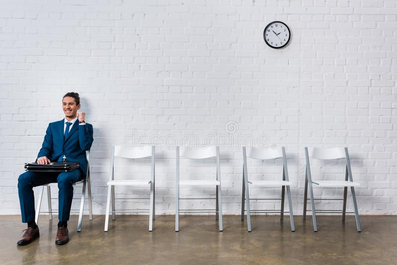 Concept of successful interview with young happy businessman. Sitting on chair stock photography