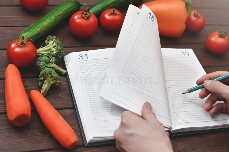 Concept suivant un régime avec un bloc-notes et un stylo entourés par un bon nombre de légumes frais sains images stock