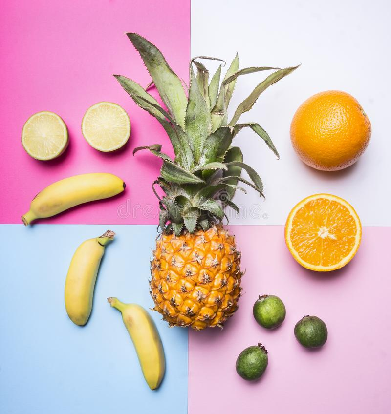 Concept of summer fruit set against a bright background mini pineapple, mango, mini bananas, lime, quince, top view stock image