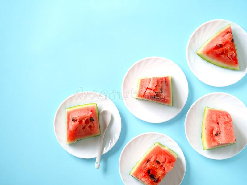 The concept of a summer holiday on a blue background. Pieces of watermelon in a plate, fruit. The view from the top.Flat lay. The concept of a summer holiday on stock image