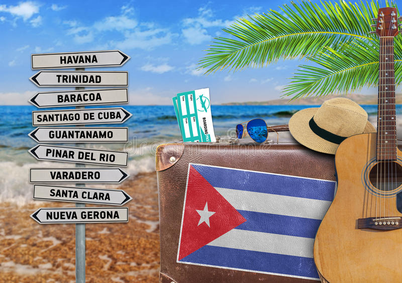 Concept of summer traveling with old suitcase and Cuba town sign royalty free stock images