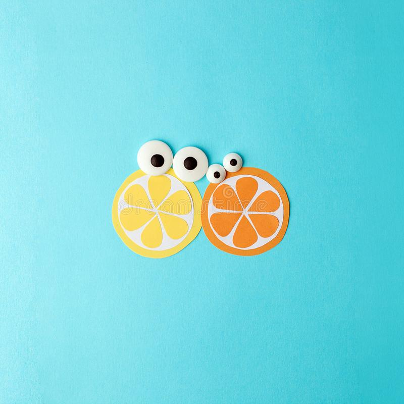 Concept of summer - two fruit from paper with cute eyes - lemon and orange on a blue background, origami modern creative idea royalty free stock photos