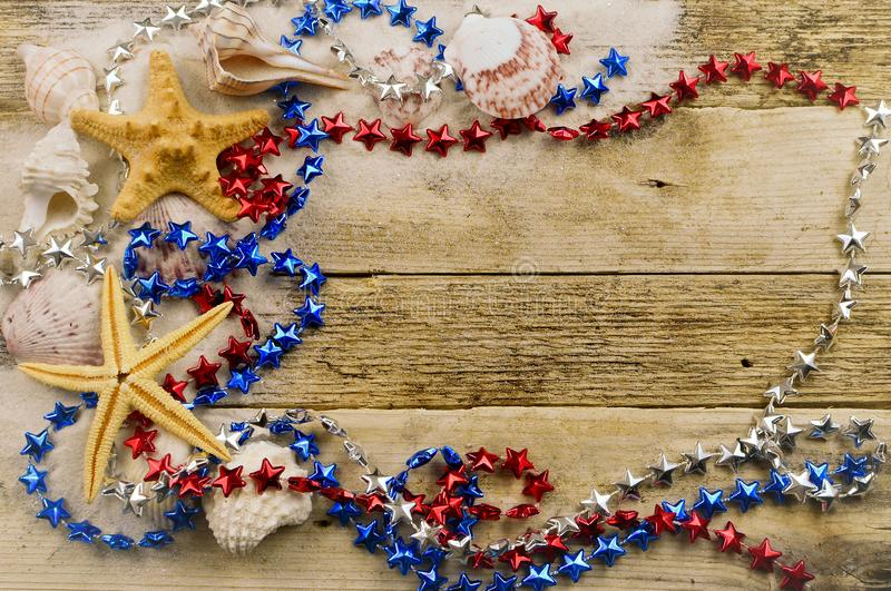 Concept for summer United States holiday of fourth of July on the beach with shells, starfish, and sand. stock image