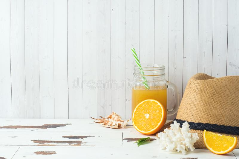 Concept summer vacation. Straw hat with Orange juice and shells. Copy space royalty free stock photos