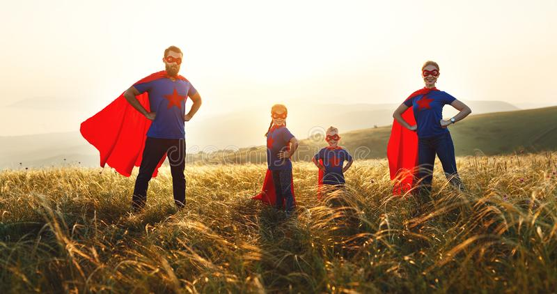 Concept of super family, family of superheroes at sunset. In nature royalty free stock photo