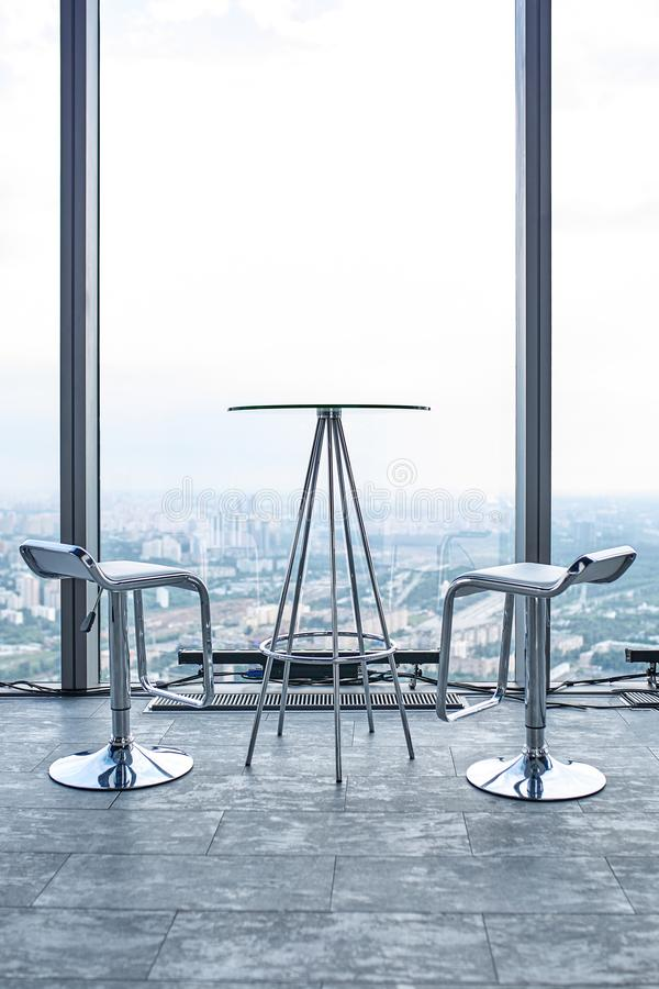 Concept talk with God. A platform on a high-rise building, a table and two chairs overlooking the sky and the city. Concept talk with God. A platform on a high royalty free stock photo