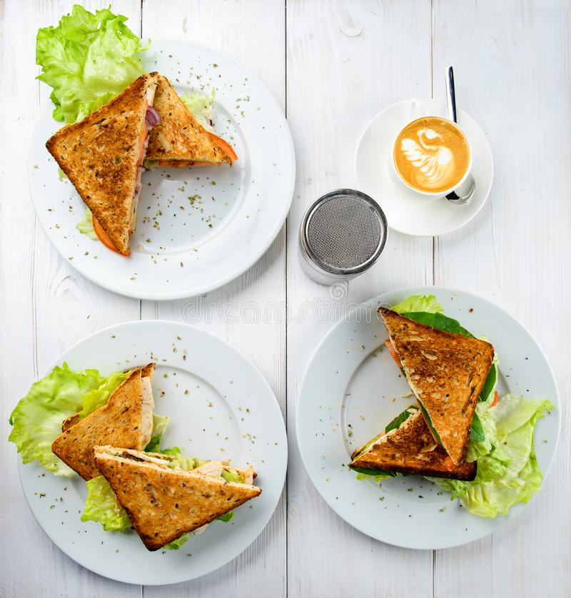 Concept of tasty breakfast or lunch time. Different sandwiches o. N plates on white rustic background, top view, flat lay stock images