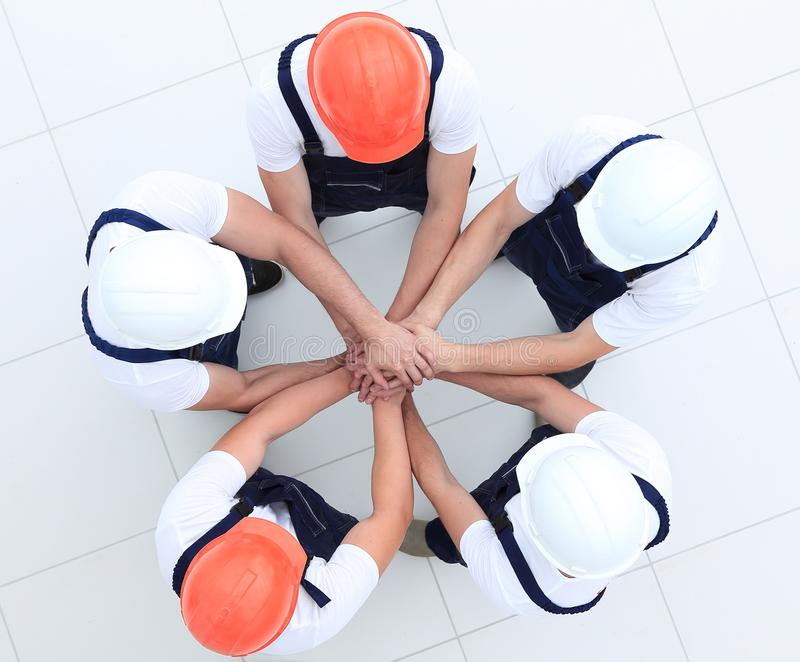 Group of construction workers with hands clasped together. Concept of the team.a close-knit group of builders royalty free stock image