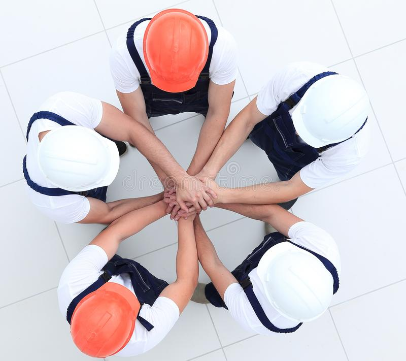 Group of construction workers with hands clasped together. Concept of the team.a close-knit group of builders stock images