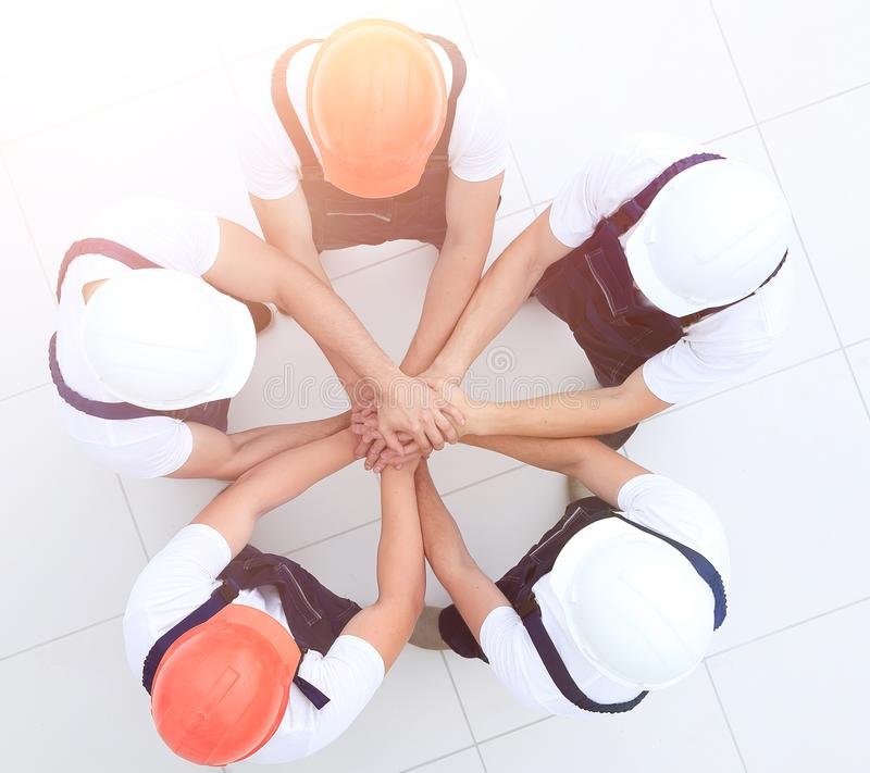 Group of construction workers with hands clasped together. Concept of the team.a close-knit group of builders stock photos