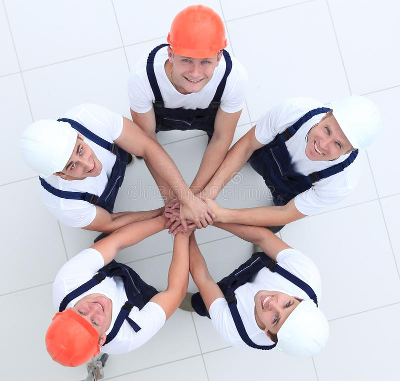 Group of construction workers with hands clasped together. Concept of the team.a close-knit group of builders stock photography